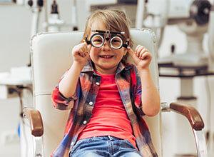 Kleiner Junge testet Brillen wegen Fehlsichtigkeiten.