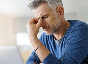 Aufgrund von Kopfschmerzen greift sich ein Mann mit schmerzverzerrtem Gesicht an die Nasenwurzel.