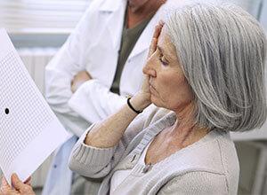 Ältere Dame hält sich ein Auge zu und wird auf Makula-Degeneration getestet.
