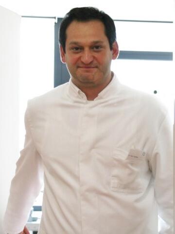 Dr. Todor Toschkov, Ihr kompetenter Augenarzt in Wien, steht in der Tür und lächelt freundlich.